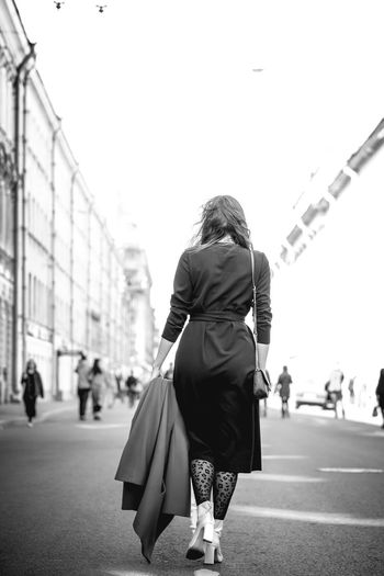 One Person Women Real People Full Length City Incidental People Lifestyles Adult Architecture Street Day Leisure Activity Walking Rear View Sky Casual Clothing Bag Built Structure Transportation Hair Outdoors Hairstyle