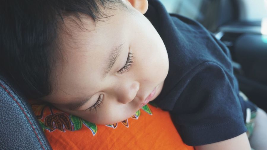 Close-up of baby boy sleeping on shoulder of mother in car