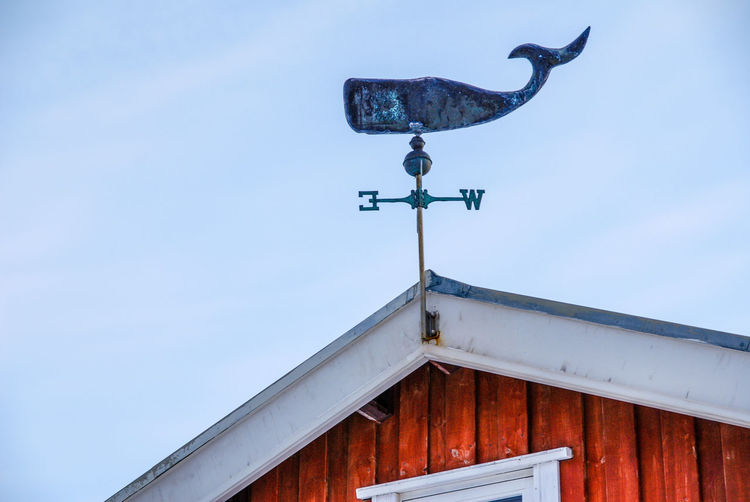 Low angle view of weather vane on house against clear sky
