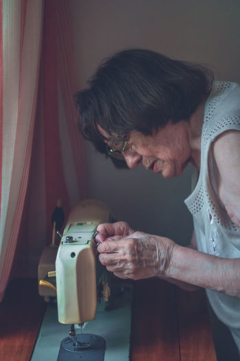 Senior woman working on sewing machine