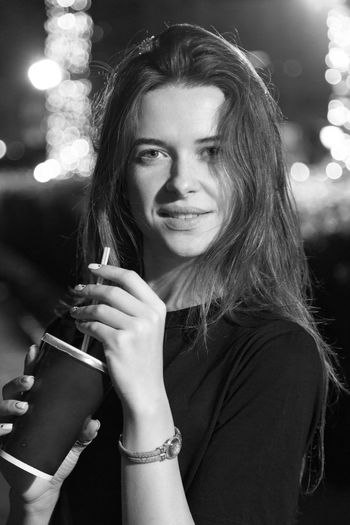 Portrait of beautiful woman holding camera at night