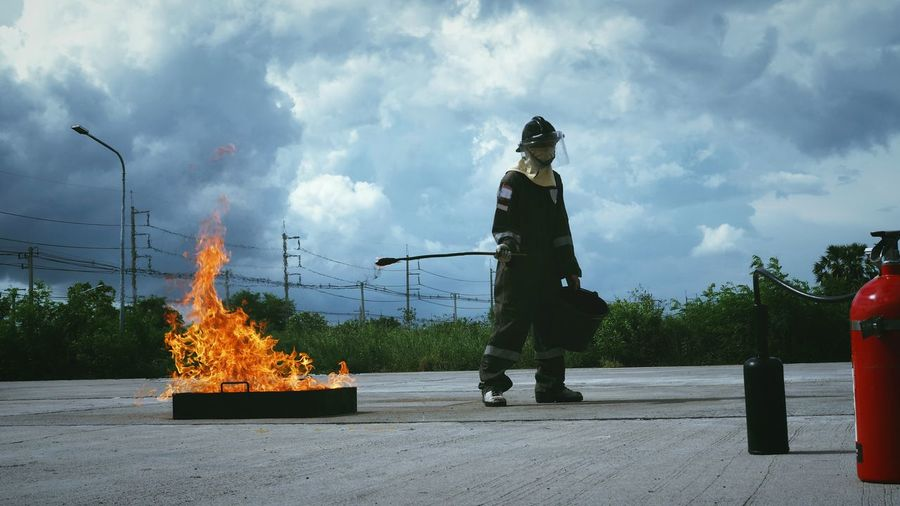 Full length of firefighter standing on road against sky