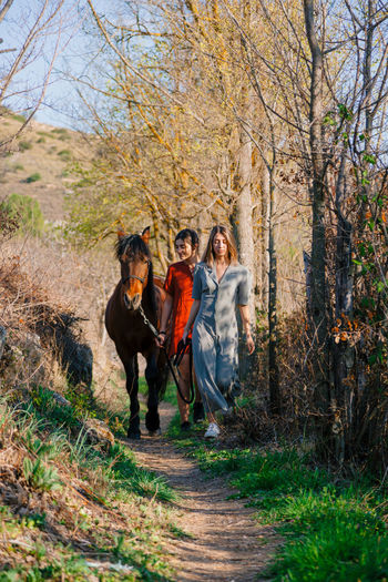 Full length of women walking with horse outdoors