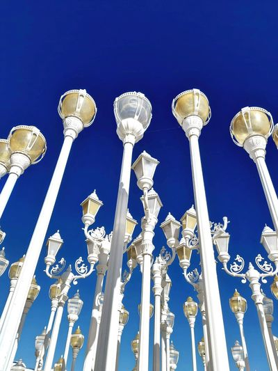 Low angle view of lighting equipment against blue sky on sunny day