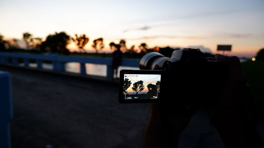 Man photographing with camera phone against sky during sunset