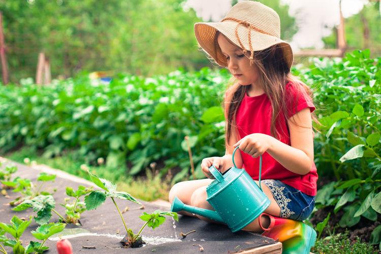 Girl wearing hat watering plants in garden