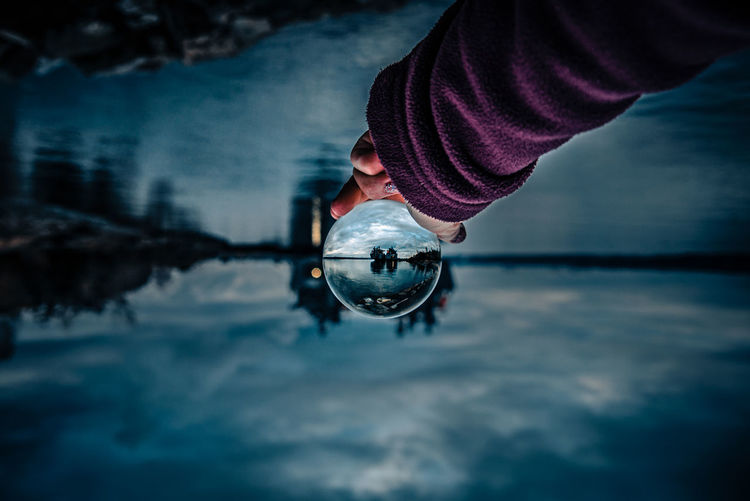 Upside down image of woman holding crystal ball against lake at night