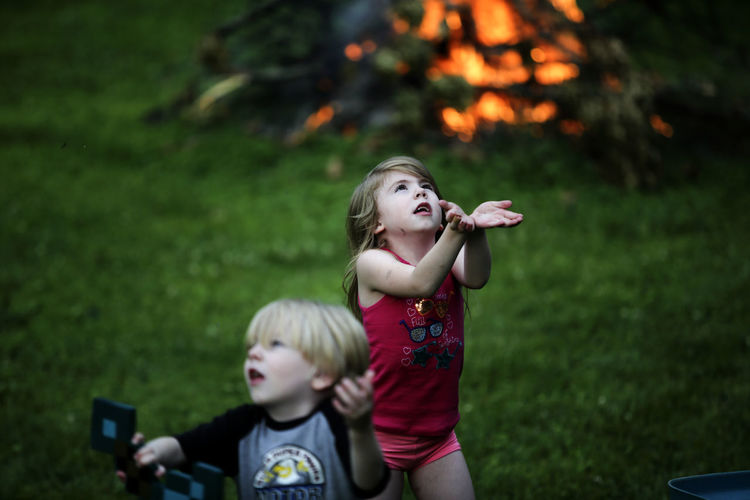 Two siblings play together near a campfire. Backyard Blond Hair Boys Campfire Camping Childhood Fireflies Girls Leisure Activity Lifestyles Outdoors Playing Real People Siblings Togetherness Two People