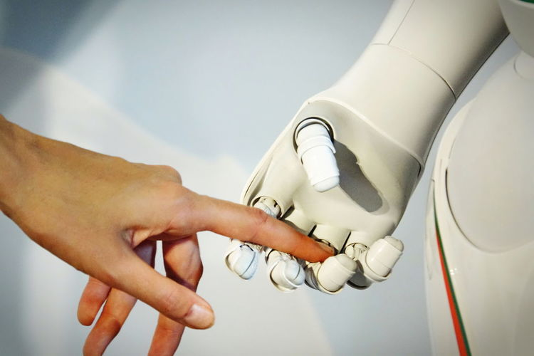 Cropped hand of woman touching robot