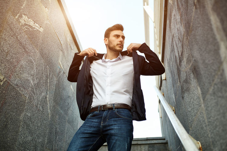 Businessman Looking Away While Standing Amidst Wall