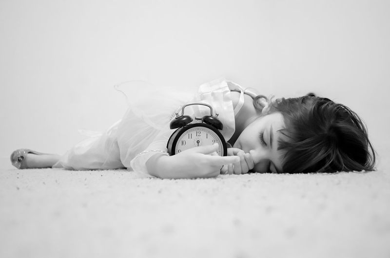 Close-up of cute girl with alarm clock lying on rug