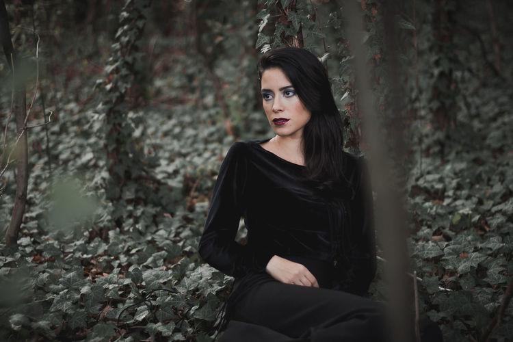 Beautiful young woman sitting on field