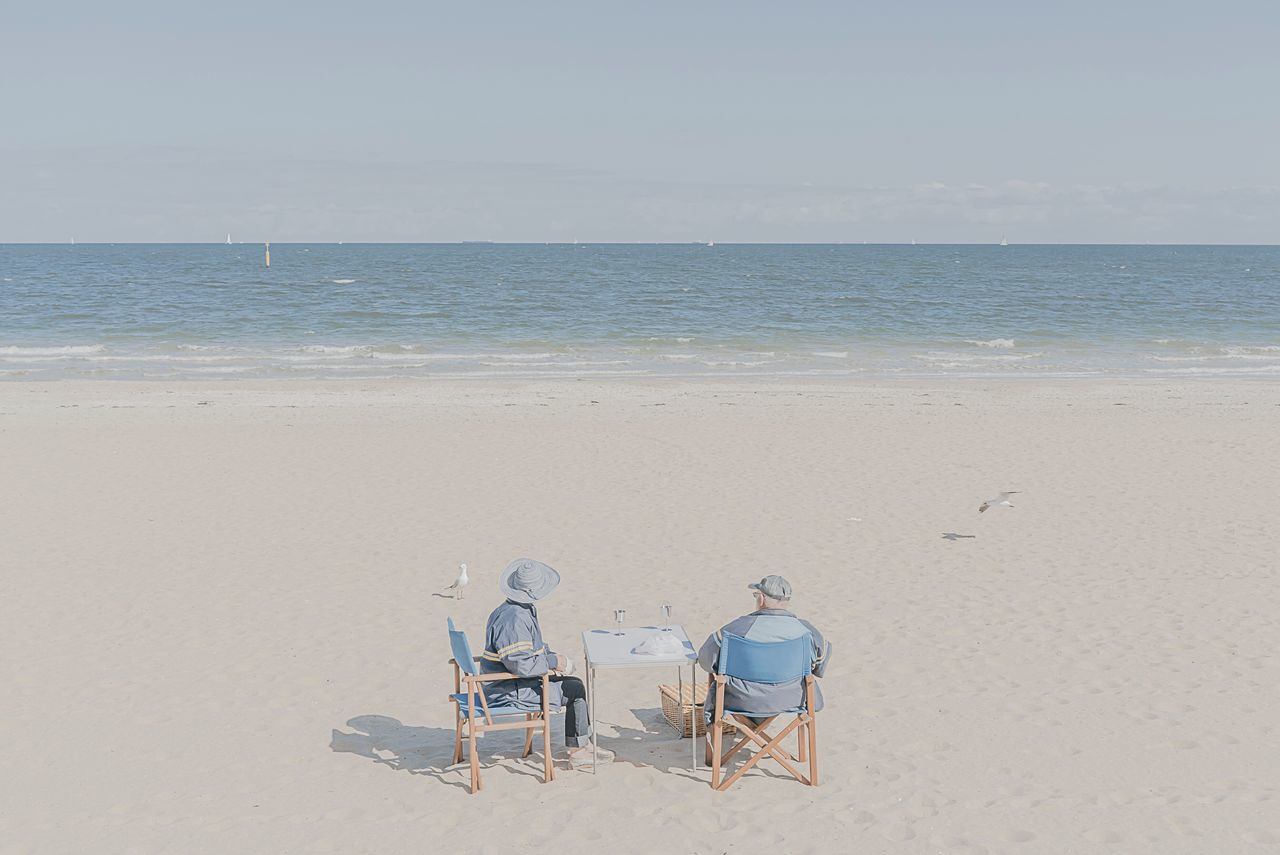 Rear view of people sitting in chairs on beach against sky