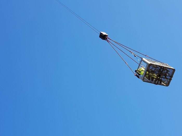 Low angle view of male workers on crane against clear blue sky