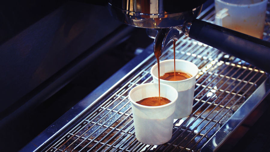 Coffee pouring from espresso maker in cup