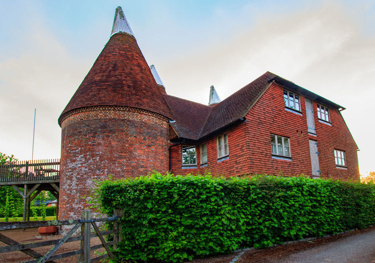 Oast house, Garden of England, Kent Architecture Built Structure Building Exterior Building Plant Sky Nature No People Day Cloud - Sky Outdoors History The Past Tree Green Color Travel Destinations Hedge Growth Wall Old Spire  Oast House Garden Of England Vivid International Rural Scene Village Farm Hops