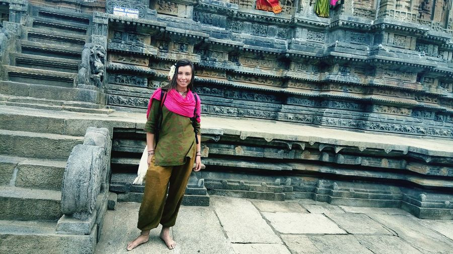 Portrait of smiling young woman standing against historic temple