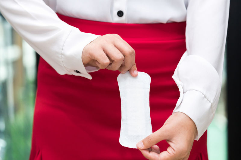 Midsection of businesswoman holding sanitary pad