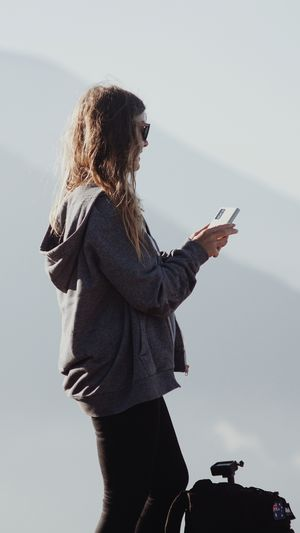 Woman using mobile phone against sky