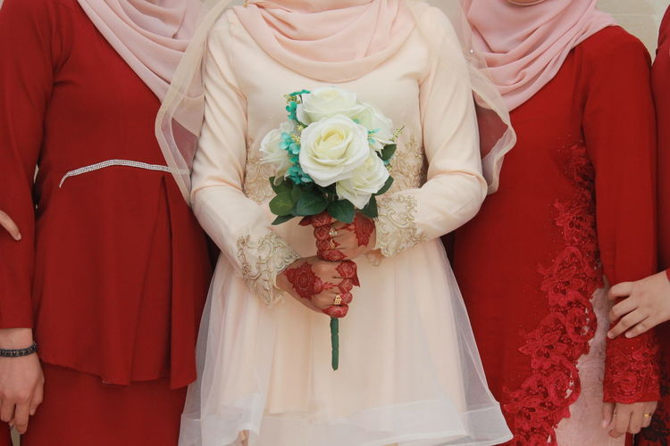 Midsection of bride holding white roses with bridesmaids