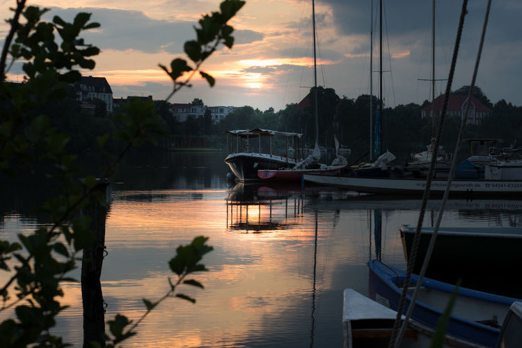 Boats moored at waterfront during sunset