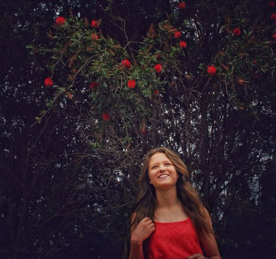 Portrait of a smiling young woman standing against trees