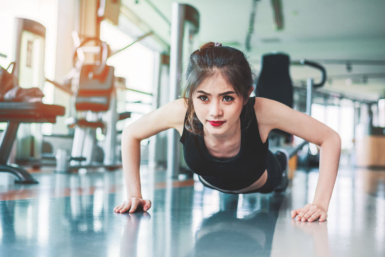 Beautiful Woman Day Exercise Equipment Exercising Flexibility Front View Full Length Gym Health Club Healthy Lifestyle Indoors  Leisure Activity Lifestyles Looking At Camera One Person People Portrait Practicing Real People Sports Clothing Sports Training Strength Young Adult Young Women