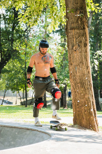 man skateboarding in a skatepark Tree Full Length Plant One Person Leisure Activity Day Sport Nature Casual Clothing Tree Trunk Trunk Men Front View Sports Equipment Sunlight Fun Shadow Lifestyles Outdoors Shorts
