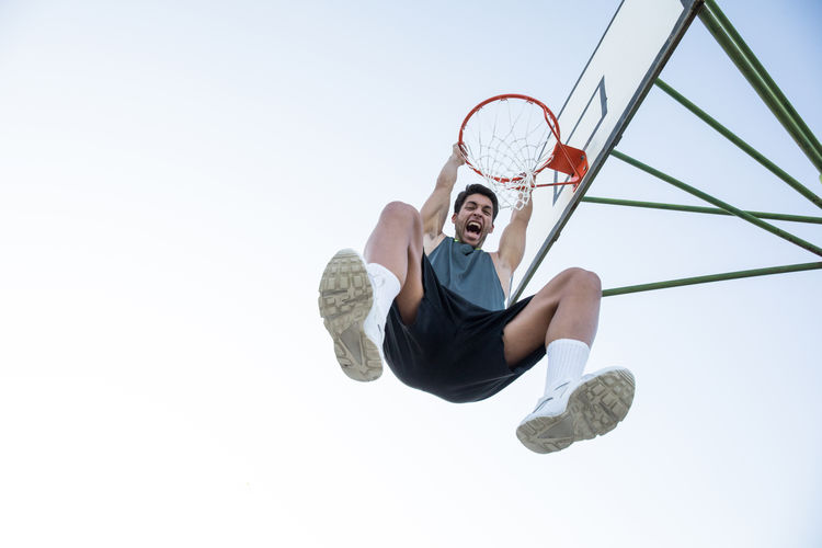 From below shot of man in sportswear hanging on hoop and shouting happily. Adult Athlete Basketball Confidence  Determination Expressive Hanging Hoop Man Motivation Sportsman Action Basket Blue Sky Confident  Excitement Expression Furious Muscular Passion Player Screaming Sport Sportsground Streetball