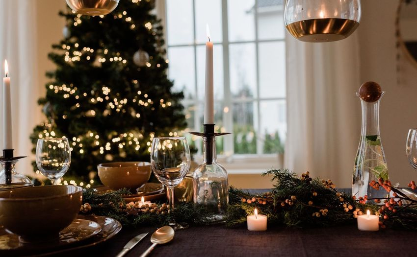 Illuminated christmas tree on table at home