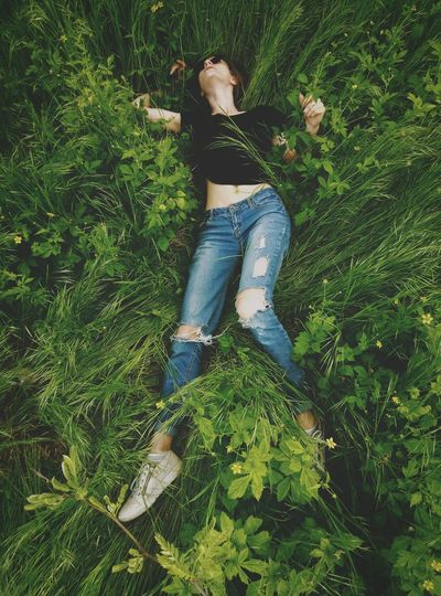 High angle view of young woman lying on plants at field