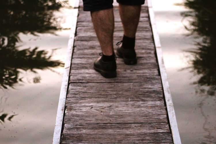 Low section of man standing on boardwalk over lake