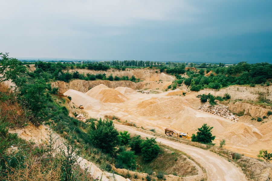 Minerals Cloud - Sky Day Environment Field Geology Growth High Angle View Industry Land Landscape Mine No People Non-urban Scene Outdoors Plant Quarry Road Sky Stone Surface Mine Tranquil Scene Transportation Truck Vehicle