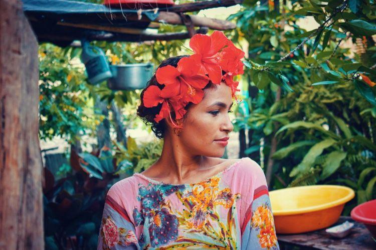 Woman wearing red flowers in hair against plants