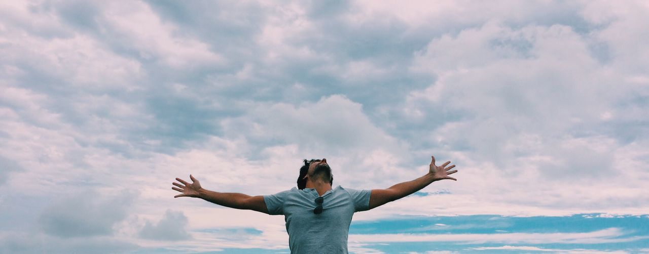 Man with arms outstretched against cloudy sky