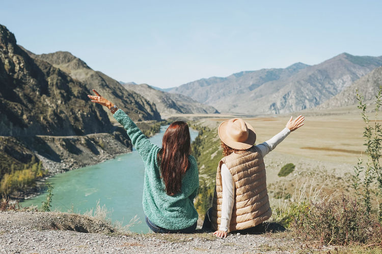 Young women travellers friends on background of turquoise katun river, altai mountains