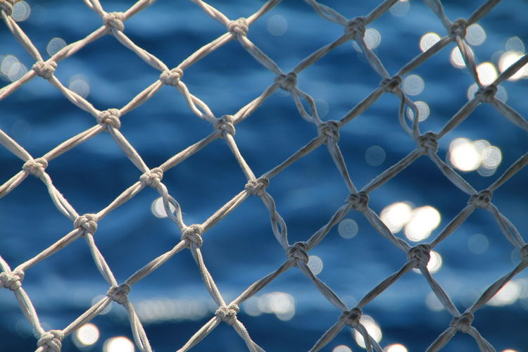 Close-up Of White Net Against Sea
