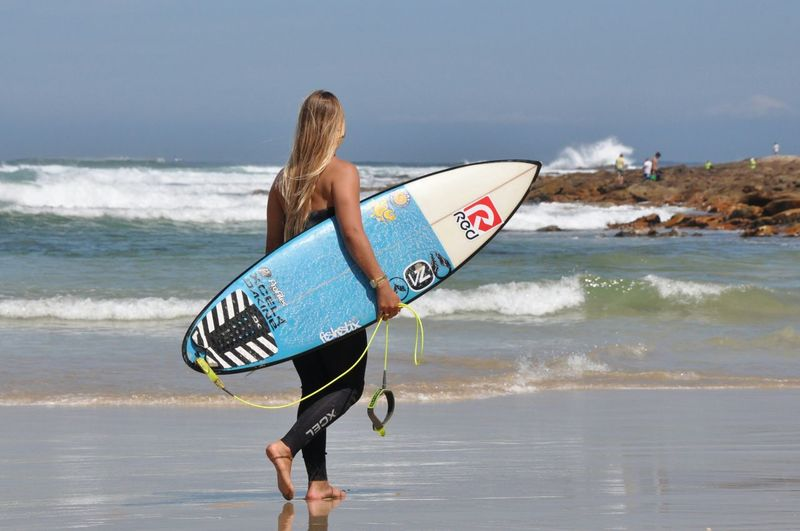 Woman holding surfboard at beach against sky