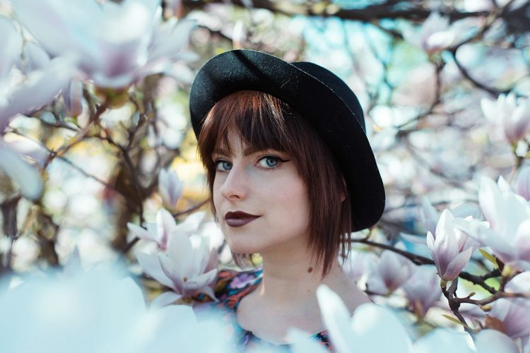 Portrait Of Young Woman Amidst Cherry Blossoms