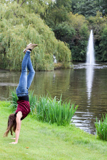 Girl doing handstand in the park Amsterdam City Park Enjoying The Sun Green Color Handstand  Plants Acrobatic Acrobatic Activity Day Enjoying Life Fun Activity Girl Doing Handstand Grass Green Colour Green Scenery Lake Lake In Park Motion Nature Park View Plant Plants And Flowers Travel Destinations Vacation Water