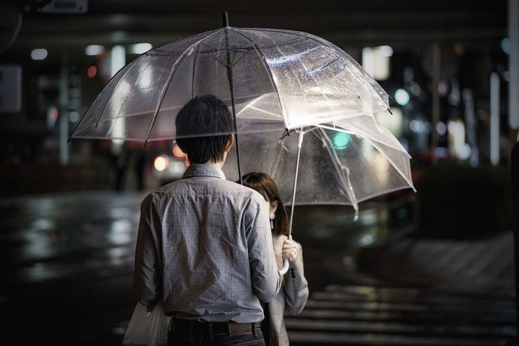 Tokyo,Japan Adult City Focus On Foreground Holding Illuminated Lifestyles Men Outdoors People Protection Rain Rainy Season Real People Rear View Security Standing Street Photography Streetphotography Umbrella Water Wet Women