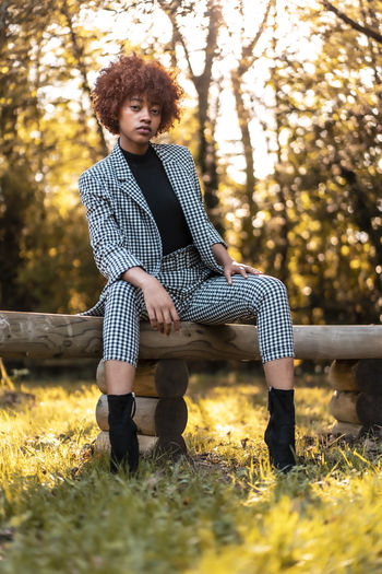 Full length of young woman sitting on bench in park