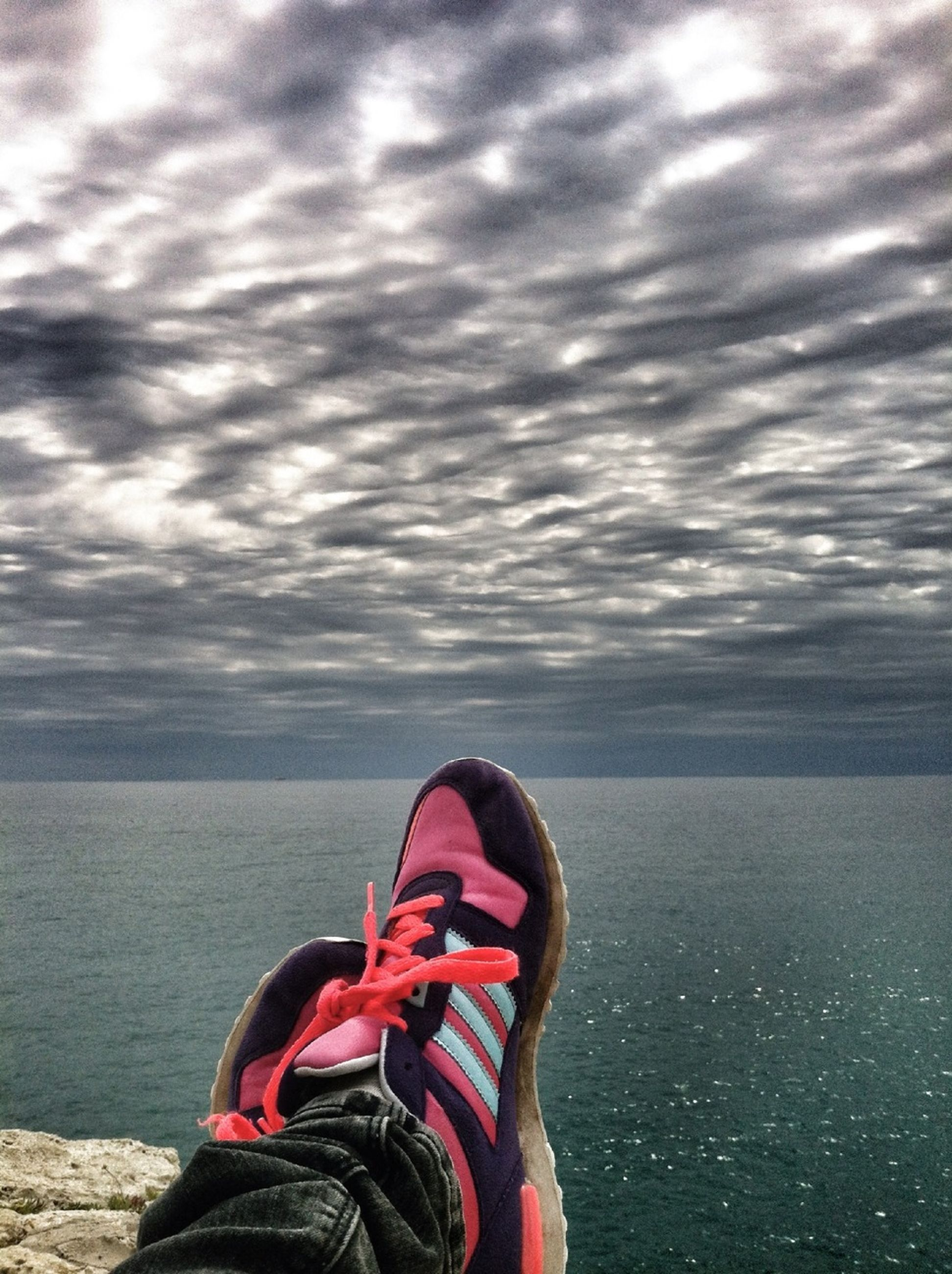 water, sky, low section, cloud - sky, person, sea, lifestyles, personal perspective, shoe, standing, cloudy, leisure activity, scenics, tranquility, horizon over water, cloud, tranquil scene, nature