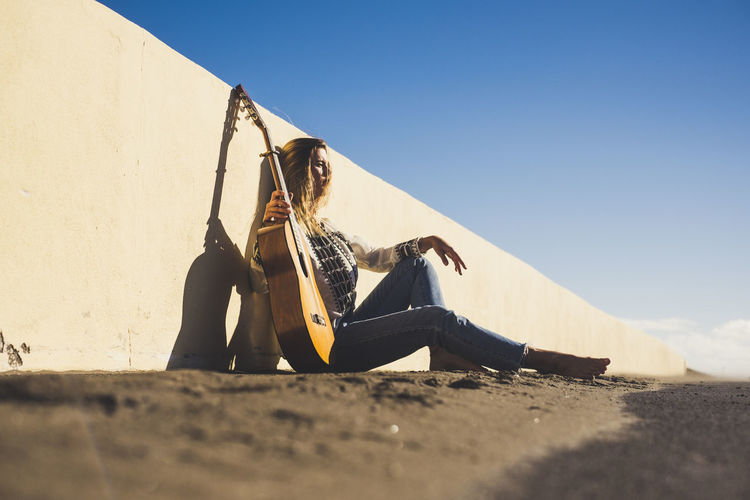 Young woman with guitar sitting on road by wall against clear sky