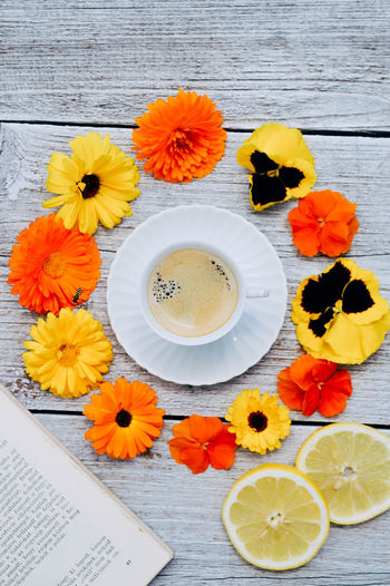 Coffee Beauty In Nature Book Close-up Crockery Directly Above Drink Flower Flower Head Flowering Plant Food And Drink Fragility Freshness High Angle View Indoors  Inflorescence Lime No People Orange Orange Color Plant Still Life Summer Table Vulnerability