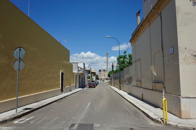 Empty Road Amidst Buildings Against Sky