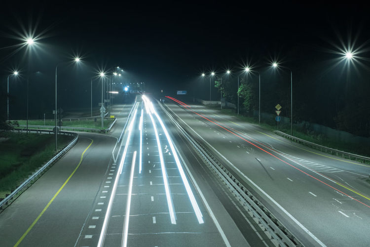 Night road with long red and white light strips from the headlights of cars.