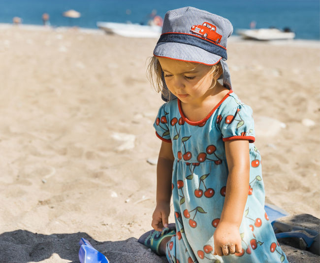 Cute girl playing in sand at beach