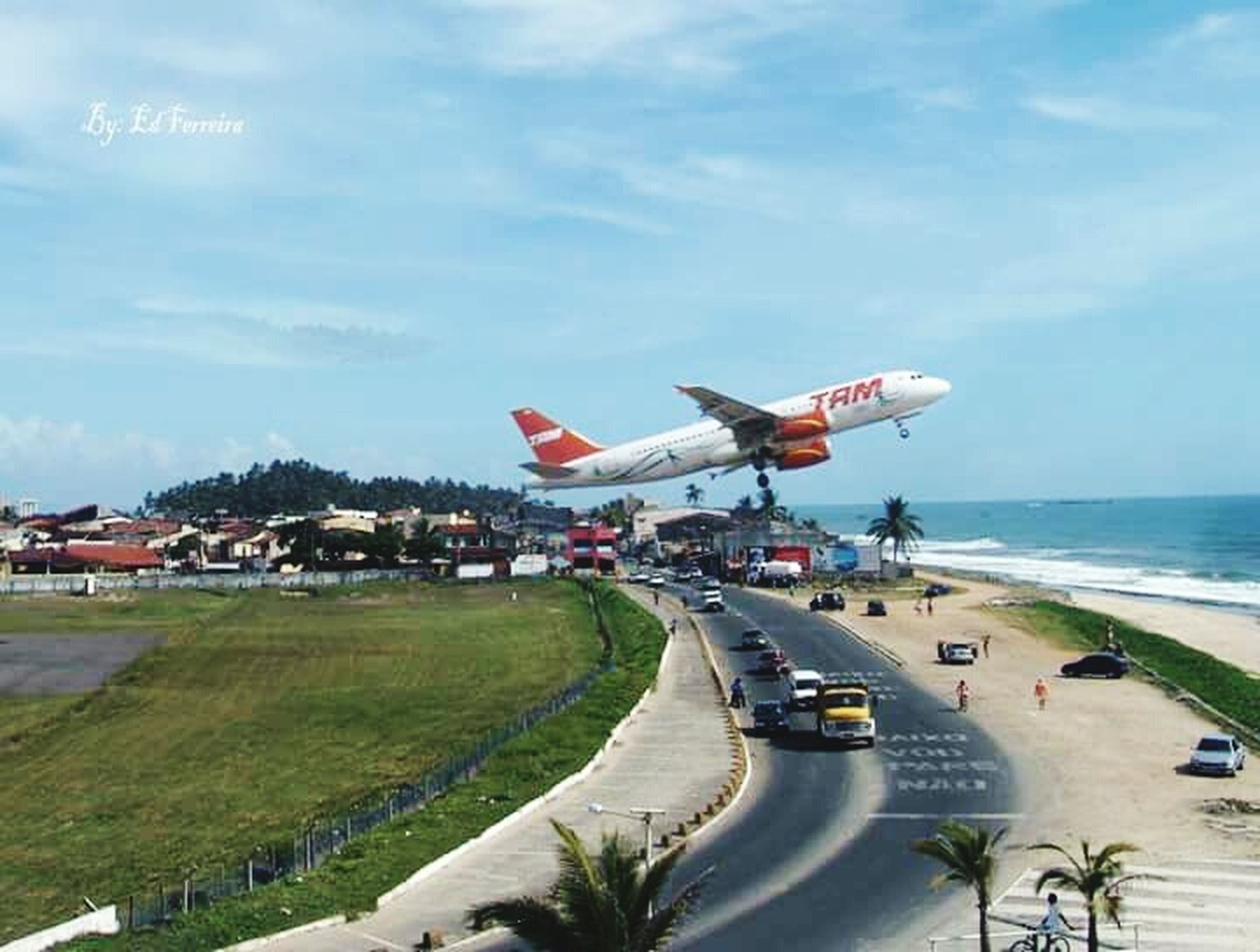 transportation, mode of transport, sky, sea, car, land vehicle, cloud - sky, travel, horizon over water, built structure, road, architecture, air vehicle, building exterior, incidental people, airplane, cloud, day, on the move, nautical vessel