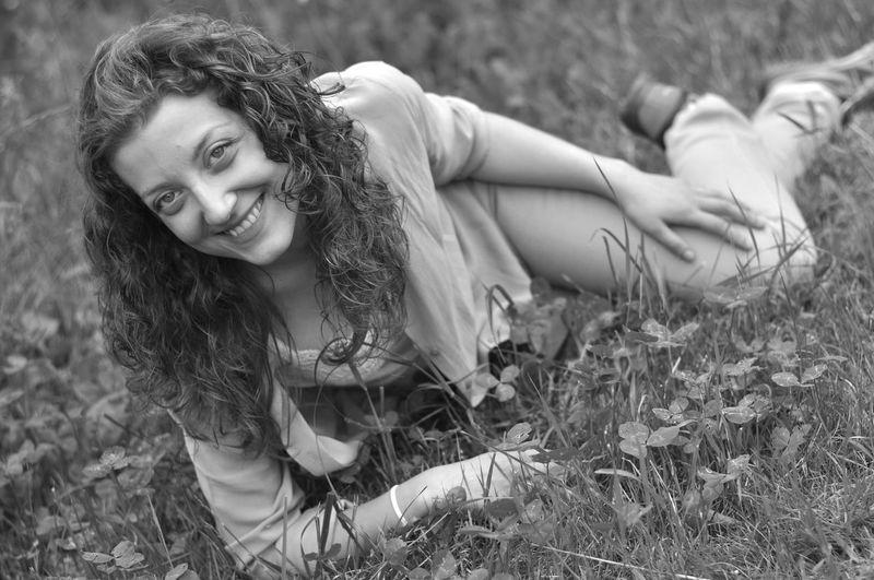 Portrait of happy woman lying on field